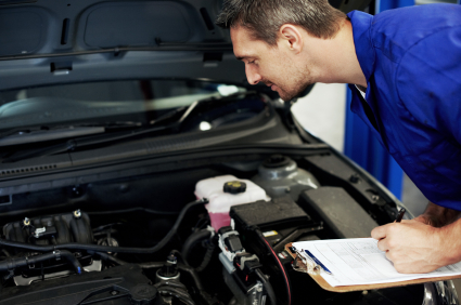Mechanic making notes on a clipboard during a fleet vehicle check