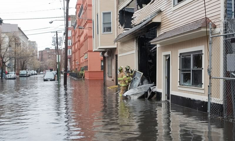 firefighters in flood next to damaged building